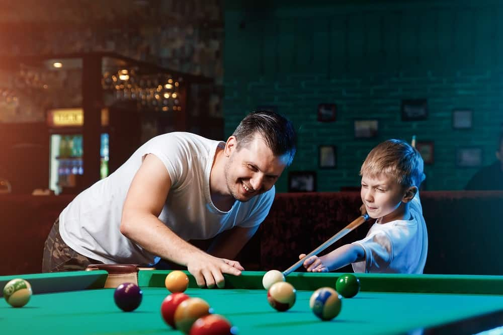Father and son play billiards