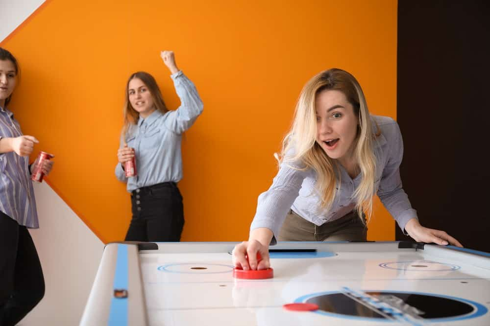 Young women playing air hockey