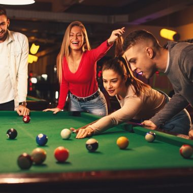 Group of friends play billiards