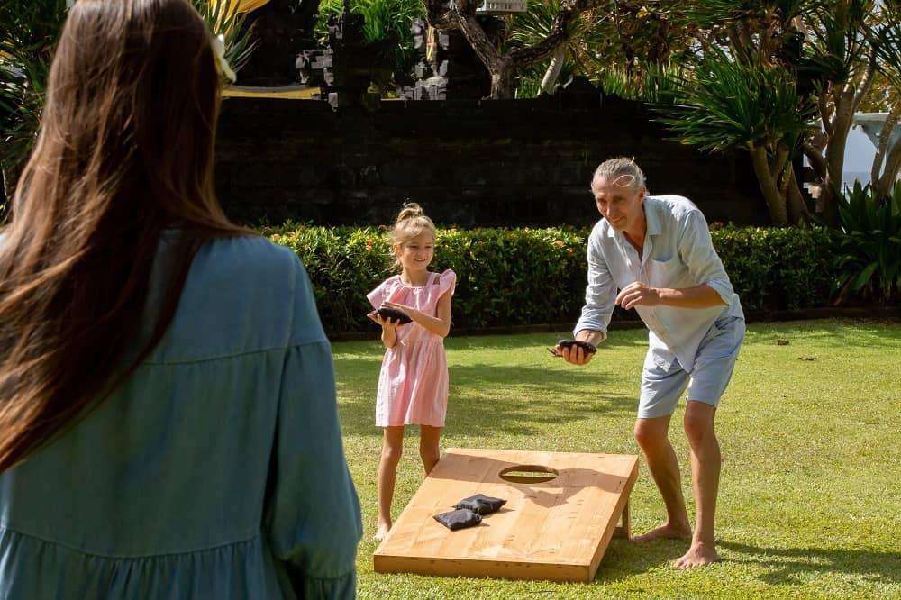 Family playing cornhole game