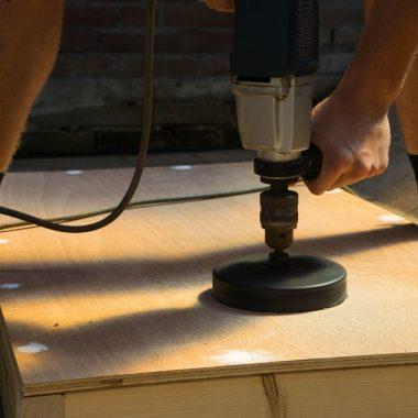 man cuts hole in DIY cornhole table