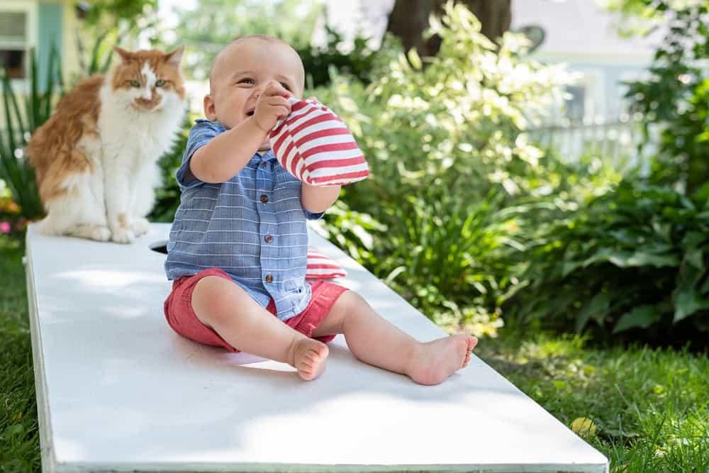 little kid sitting on cornhole table