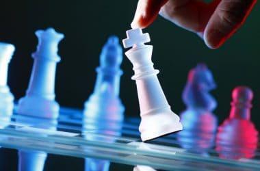Finger tilting a glass chess piece